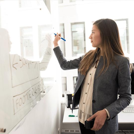 Frau schreibt an Whiteboard